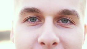 Het close-upportret van de glimlachende aantrekkelijke Kaukasische mens met grijze ogen bekijkt camera Langzame Motie 3840x2160 stock video