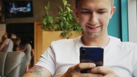 Het close-upportret van de jonge mens gebruikt mobiele telefoon in koffie stock videobeelden