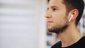 Het close-upportret van de jonge mens met hoofdtelefoons luistert aan muziek bij airpods en het glimlachen