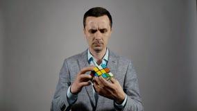 Het close-upportret van een jonge bedrijfsmens probeert om de Kubus van een Rubik te assembleren stock videobeelden