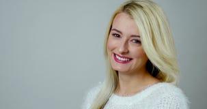 Het close-upportret van een jonge blondevrouw maakt een tedere elegante glimlach stock video
