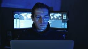 Het close-upportret van een Mensen Professionele IT Programmeur in een datacentrum vulde met de monitorschermen De hakkerwerken b stock video
