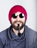 Het close-upportret van een positieve knappe jonge gebaarde hipster in roze gebreide hoed die een pijp roken, drukt divers uit royalty-vrije stock fotografie