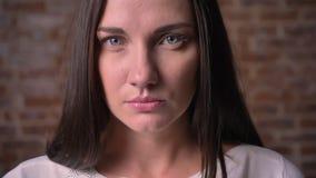 Het close-upportret van een vrouw, die ernstig op in de camera op a let bricken achtergrond stock video