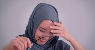 Het close-upportret van gelukkige moslimonderneemster in hijab houdt haar oogglazen en het lachen zijnd uiterst blij stock footage