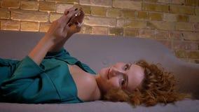 Het close-upportret van gember hethaired meisje liggen bij bank het letten op in smartphone draait aan camera op comfortabel huis stock footage