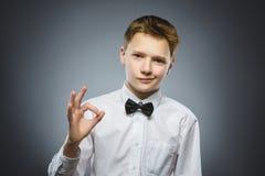Het close-upportret van het knappe tiener glimlachen en toont O.k. over grijze achtergrond royalty-vrije stock afbeelding