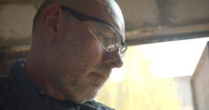 Het close-upportret van hogere mannelijke timmerwerkmeester werkt bij houten fabriek die de kortzaag drukken snijdend het hout stock video