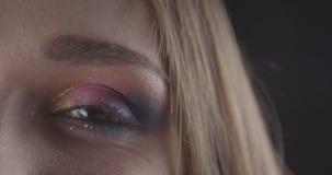 Het close-upportret van jong charmant Kaukasisch kort haired vrouwelijk gezicht met ogen met leuk schittert make-up bekijkend stock video