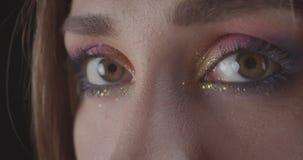 Het close-upportret van jong charmant Kaukasisch kort haired vrouwelijk gezicht met ogen met leuk schittert make-up bekijkend stock videobeelden