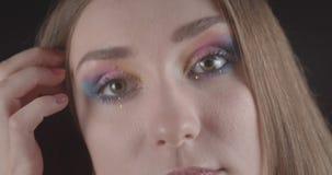 Het close-upportret van jong grappig Kaukasisch kort haired vrouwelijk gezicht met ogen met leuk schittert make-up met achtergron stock video