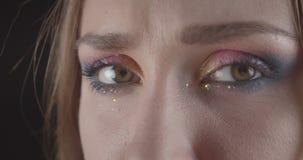 Het close-upportret van jong grappig Kaukasisch kort haired vrouwelijk gezicht met ogen met schittert make-up met achtergrond stock footage