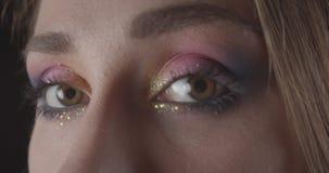 Het close-upportret van jong Kaukasisch kort haired vrouwelijk gezicht met ogen met vrij schittert make-up bekijkend camera met stock video