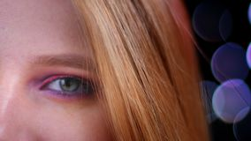Het close-upportret van jong vrij Kaukasisch vrouwelijk gezicht met half van toepassing geweest schittert roze make-up bekijkend  stock video