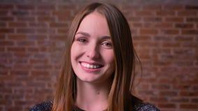 Het close-upportret van jonge gembervrouw die met gelukkige ogen delightfully aan camera glimlachen bricken achtergrond stock videobeelden