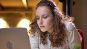 Het close-upportret van jonge krullend-haired vrouw bored uiterst in bureau het doen leunen op stoel en het tonen van haar vermoe stock footage