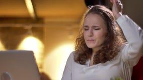 Het close-upportret van jonge krullend-haired vrouw doet leunen op stoel in sterke frustratie en teleurstelling in bureau stock videobeelden