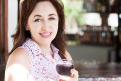 Het close-upportret van mooie gelukkige midden oude vrouw houdt een glas wijn bij de toevlucht op haar vakantie, de zomerconcept royalty-vrije stock foto