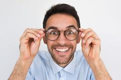 Het close-upschot die van verbaasd jong Europees knap mannetje, door ronde bril kijken, raakt rand van glazen, glimlachend met stock fotografie