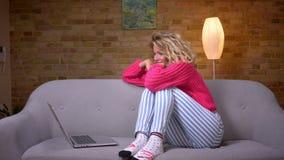 Het close-upschot van huisvrouw in roze sweater koestert haar knieën die video hebben uitnodigt laptop in huisatmosfeer stock videobeelden