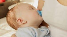 Het close-upschot van leuke babyjongen met soother viel in slaap op moedershanden stock videobeelden