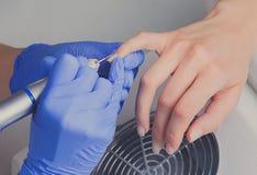 Het close-upschot van manicure in blauwe rubberhandschoenen maakt opperhuid op vrouwelijke spijkers schoon gebruikend een malensn stock afbeeldingen