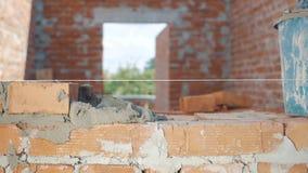 Het close-upschot van Metselaar bouwt muur in huis stock footage