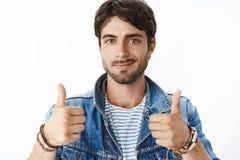 Het close-upschot van tevreden en gelukkig jong aantrekkelijk mannetje met blauw ogen en varkenshaar in denimjasje het opheffen b royalty-vrije stock foto