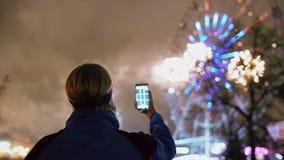 Het close-upsilhouet van mens die en op vuurwerk letten de fotograferen explodeert in openlucht op smartphonecamera stock video