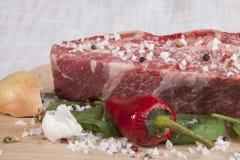 Het close-upstuk van vers marmerrundvlees, Spaanse peperpeper, peterselie, ui, knoflook, ribben ligt op een houten dienblad Royalty-vrije Stock Afbeeldingen