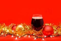 Het cognacglasglas donker bier met Kerstmis steekt snuisterijen en klatergoud op rode achtergrond aan royalty-vrije stock afbeeldingen