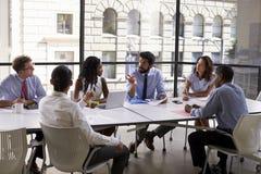 Het collectieve bedrijfsteam en de manager in een vergadering, sluit omhoog stock foto