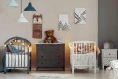 Het comfortabele binnenland van de babyslaapkamer met witte en grijze voederbakken, ladenkast en kleine nightstandlijst royalty-vrije stock foto's