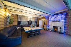 Het comfortabele binnenland van een buitenhuis met een open haard Stock Afbeelding