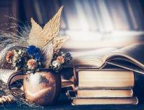 Het comfortabele huislandschap met de herfstboeket met bladeren en daling bloeit in kop met stapel boeken stock foto