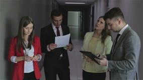 Het commerciële team bekijkt de documenten die zich in bureaugang bevinden stock footage