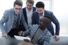 Het commerciële team bespreekt de informatie gebruikend een digitale tablet stock foto's