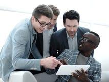 Het commerciële team bespreekt de informatie gebruikend een digitale tablet stock afbeeldingen