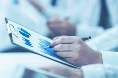 Het commerciële team die digitale tablet gebruiken voert analyse van marketing grafiek uit stock foto's