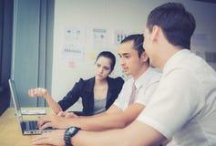 Het commerciële team die een vergadering hebben die laptop met behulp van tijdens een vergadering en stelt voor Royalty-vrije Stock Foto's
