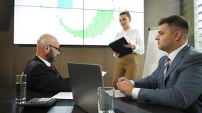 Het commerciële team geeft een presentatie van een nieuw financieel project voor de partners van het bedrijf in langzame motie stock videobeelden