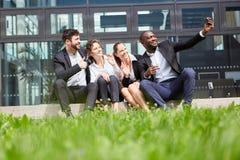 Het commerciële team maakt selfie met smartphone stock foto