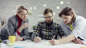 Het commerciële team van het jonge vastberaden mensen genieten die, millennials groepeert het spreken hebbend pret in comfortabel stock video
