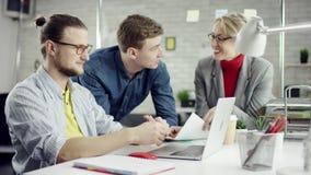Het commerciële team van jongeren genieten die, millennials groepeert het spreken hebbend pret in comfortabel goed bureau, samenw stock videobeelden