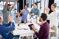 Het commerciële team vieren succes samen op werkplaats in bureau stock afbeelding