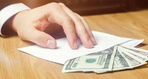 Het concept corruptie en omkoperij, wet en geld Donkere zaken De zakenman ontvangt geld in een envelop Steekpenning in de vorm stock fotografie