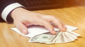 Het concept corruptie en omkoperij, wet en geld Donkere zaken De zakenman ontvangt geld in een envelop Steekpenning in de vorm royalty-vrije stock foto's
