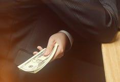 Het concept corruptie en omkoperij, wet en geld Donkere zaken De zakenman ontvangt geld - koop in de vorm van dollar om stock afbeeldingen
