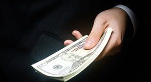 Het concept corruptie en omkoperij, wet en geld Donkere zaken De zakenman ontvangt geld - koop in de vorm van dollar om royalty-vrije stock fotografie