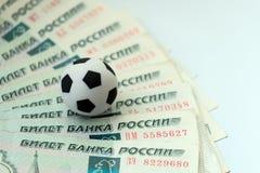 Het concept corruptie, steekpenningen of sporten het wedden Een voetbalbal op Russische bankbiljetten met een nominale waarde van stock foto